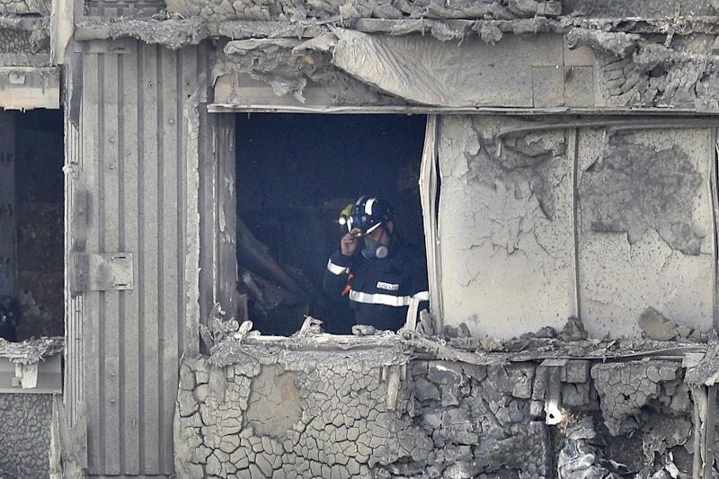 A firefighters looks out of the window of the gutted Grenfell Tower (Getty Images)