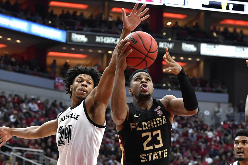 Florida State guard M.J. Walker (23) attempts to shoot past the defense of Louisville forward Dwayne Sutton (24) during the first half of an NCAA college basketball game in Louisville, Ky., Saturday, Jan. 4, 2020. (AP Photo/Timothy D. Easley)