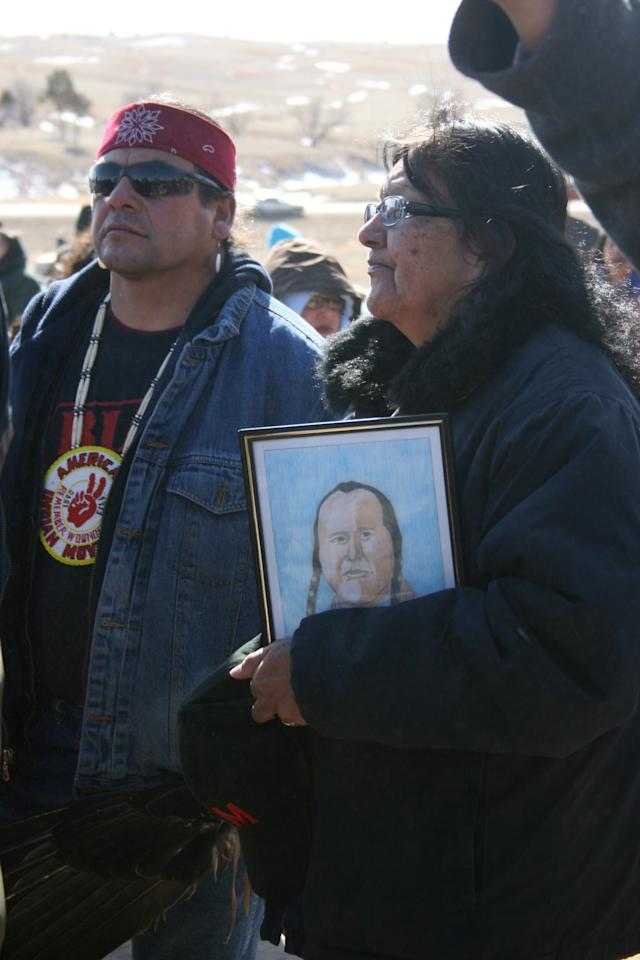 A woman holds a drawing of former American Indian Movement leader Russell Means Wednesday, Feb. 27, 2013 in Wounded Knee, S.D. Wednesday marked the 40th anniversary of the start of the 71-day occupation in the village of Wounded Knee on the Pine Ridge Indian Reservation. Hundreds of AIM members and other supporters turned out for a day of ceremonies to commemorate the anniversary of the fatal standoff that drew national attention to the impoverished reservation and the plight of local tribes.. Means died in October at the age of 72 from throat cancer. (AP Photo/Kristi Eaton)