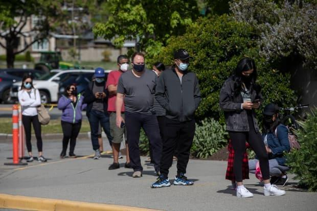 People line up outside Killarney Community Centre to receive a COVID-19 vaccination in their 'hot spot' neighbourhood of Vancouver on May 11. (Ben Nelms/CBC - image credit)