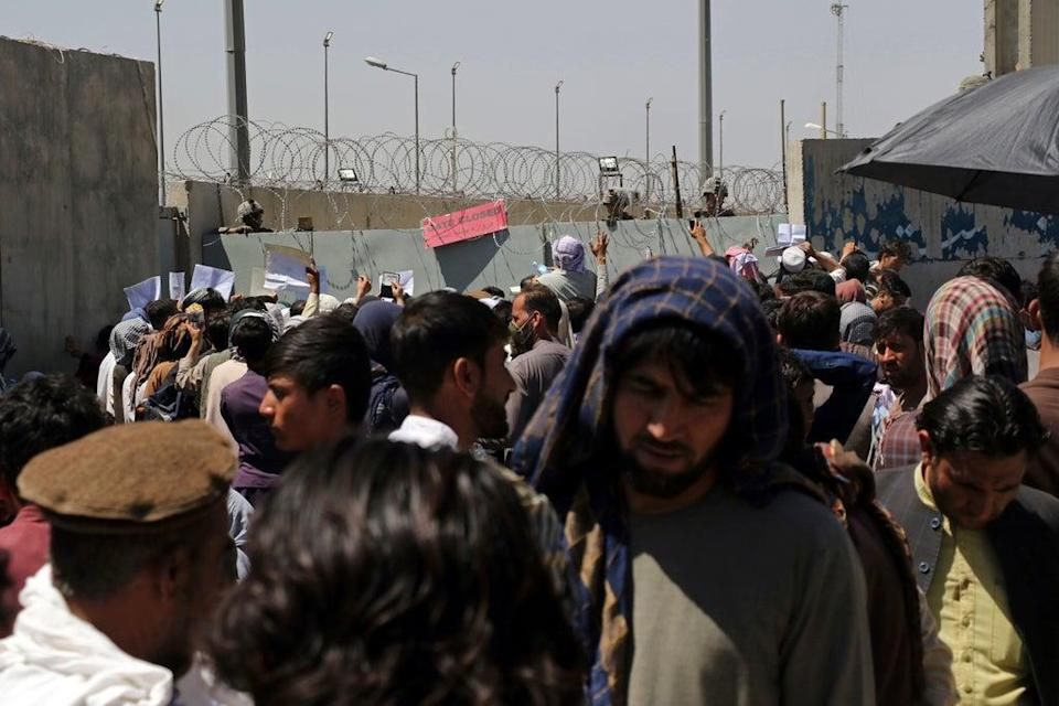 Hundreds of people gather near an evacuation control checkpoint on the perimeter of the Hamid Karzai International Airport, in Kabul (Wali Sabawoon/AP) (AP)