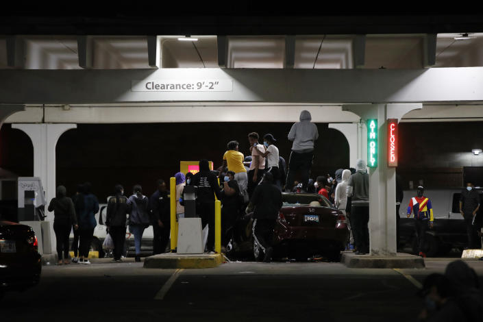 People loot a Wells Fargo ATM, Friday, May 29, 2020, in Minneapolis. Protests continued following the death of George Floyd, who died after being restrained by Minneapolis police officers on Memorial Day. (AP Photo/John Minchillo)