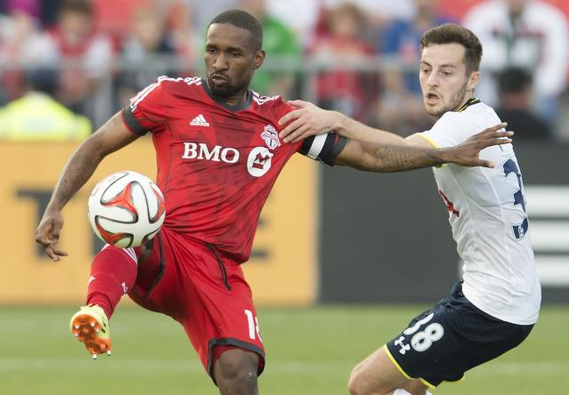 Toronto FC's Jermain Defoe, left, and Tottenham Hotspur's Ryan Mason battle for the ball during the first half of a friendly soccer match in Toronto on Wednesday, July 23, 2014. (AP Photo/The Canadian Press, Darren Calabrese)