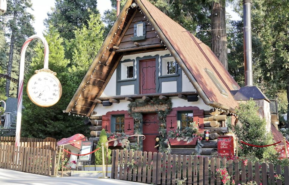 An A-frame alpine house decorated with a candy cane clock stand at SkyPark at Santa's Village in Lake Arrowhead.