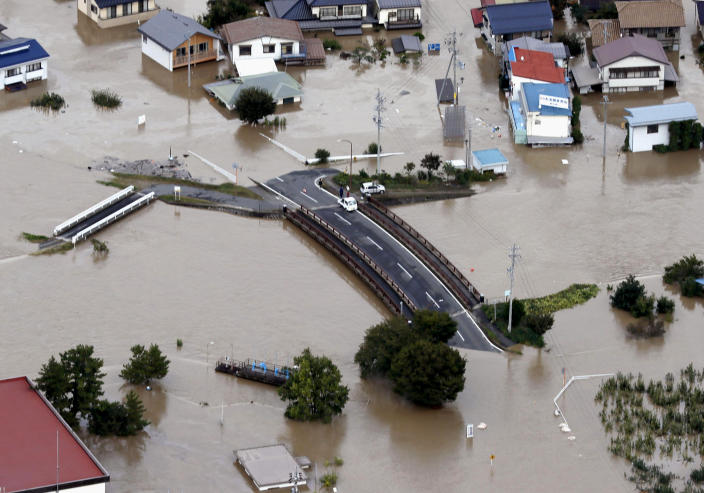 Cars are stranded on a road as the city is submerged in muddy waters after an embankment of the Chikuma River broke, in Nagano, central Japan, Sunday, Oct. 13, 2019. Rescue efforts for people stranded in flooded areas are in full force after a powerful typhoon dashed heavy rainfall and winds through a widespread area of Japan, including Tokyo.(Yohei Kanasashi/Kyodo News via AP)