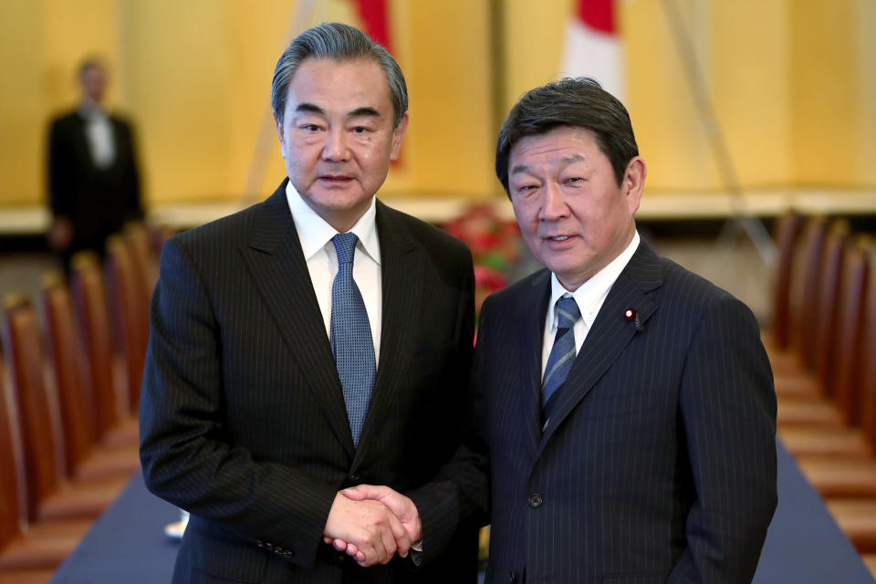 FILE - In this Nov. 25, 2019, file photo, Chinese Foreign Minister Wang Yi, left, poses with his Japanese counterpart Toshimitsu Motegi for a photo prior to a meeting in Tokyo. Motegi announced Friday, Nov. 20, 2020 that his Chinese counterpart Wang will visit Tokyo next week as the two Asian powers discuss ways to resume bilateral visits to revive their pandemic-hit economies and other regional issues. (Behrouz Mehri/Pool Photo via AP)