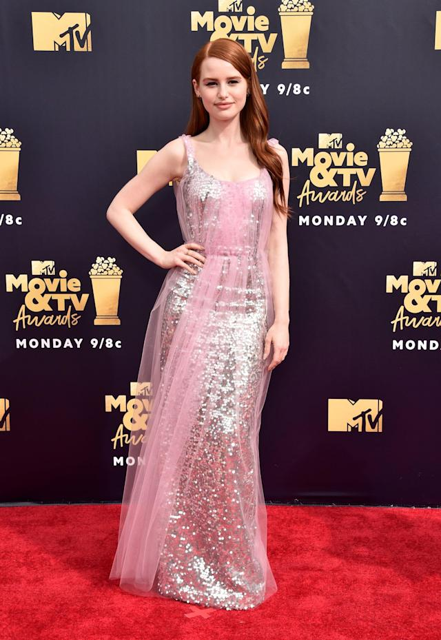 <p>Wearing a sparkly pink dress.</p>