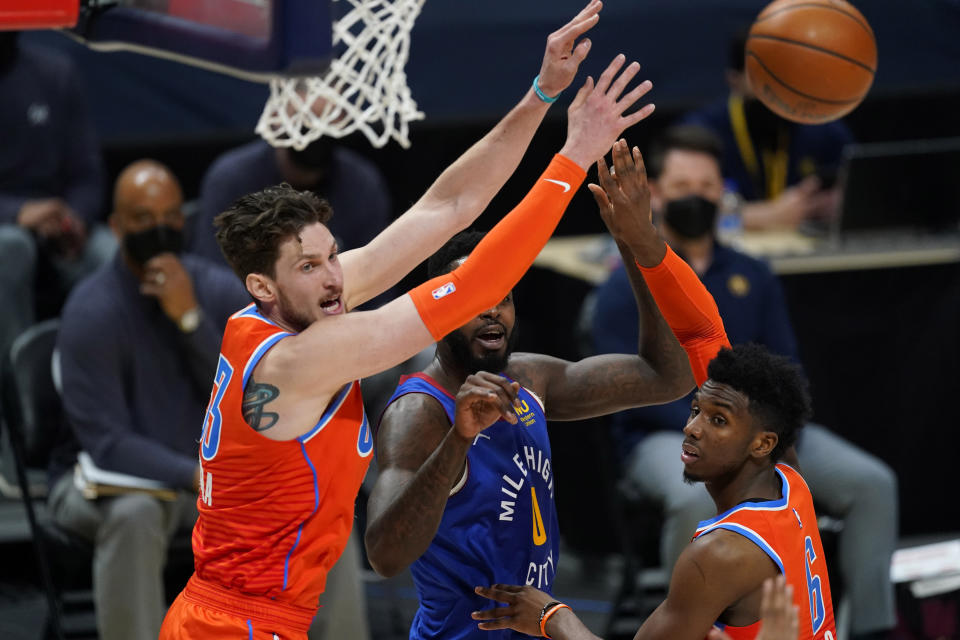 Denver Nuggets forward JaMychal Green, center, passes the ball as Oklahoma City Thunder center Mike Muscala, left, and guard Hamidou Diallo defend in the first half of an NBA basketball game Friday, Feb. 12, 2021, in Denver. (AP Photo/David Zalubowski)
