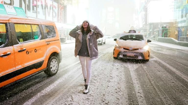 A tourist stands under the snow in Times Square in New York City, December 16, 2020