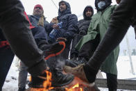 Migrants warm their feet by a fire at the Lipa camp northwestern Bosnia, near the border with Croatia, Saturday, Dec. 26, 2020. Hundreds of migrants are stranded in a burnt-out squalid camp in Bosnia as heavy snow fell in the country and temperatures dropped during a winter spell of bad weather after fire earlier this week destroyed much of the camp near the town of Bihac that already was harshly criticized by international officials and aid groups as inadequate for housing refugees and migrants.(AP Photo/Kemal Softic)