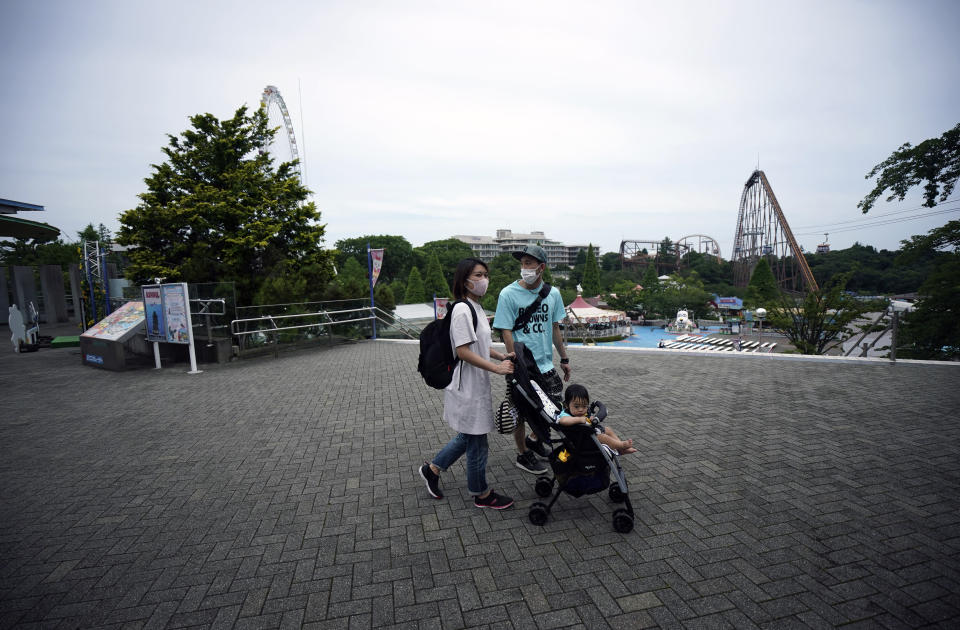 FILE - In this June 16, 2020, file photo, a family walks at the recently reopened Yomiuriland amusement park in Tokyo. Japan's economy is opening cautiously, with social-distancing restrictions amid the coronavirus pandemic. (AP Photo/Eugene Hoshiko, File)