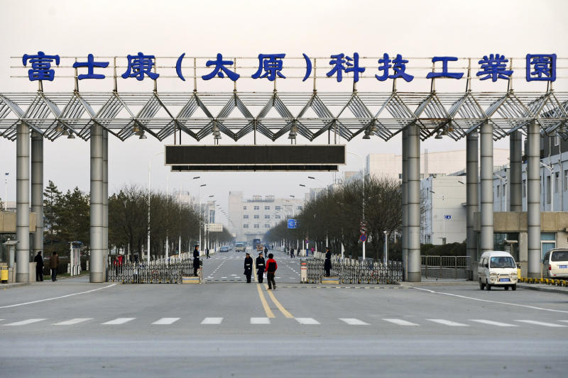 In this Nov. 22, 2011 photo, security guards stand at a gate of Foxconn's industrial zone in Taiyuan, the capital of Northern China's Shanxi province. The company that makes Apple's iPhones suspended production at a factory in China on Monday, Sept. 25, 2012, after a brawl by as many as 2,000 employees at a nearby dormitory injured 40 people. The facility will reopen Tuesday, Sept. 26, 2012. (AP Photo) CHINA OUT