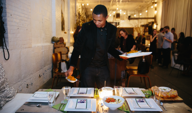 Boubacar Diallo serves food he prepared at an event for Emma's Torch.