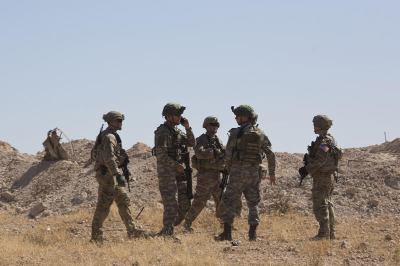 FILE - This Sept. 8, 2019 file photo, Turkish forces survey the so-called safe zone during their first joint ground patrol with U.S. forces on the Syrian side of the border with Turkey, near Tal Abyad, Syria. The region of northeastern Syria, where the Turkish president intends to launch an operation to carve out a safe zone, is one of the most combustible in Syria's long-running civil war. A U.S. troop withdrawal and Turkish assault on the area risks re-igniting fighting in a corner of Syria only recently stabilized and where sleeper cells of the Islamic State group continue to operate. (AP Photo/Maya Alleruzzo, File)