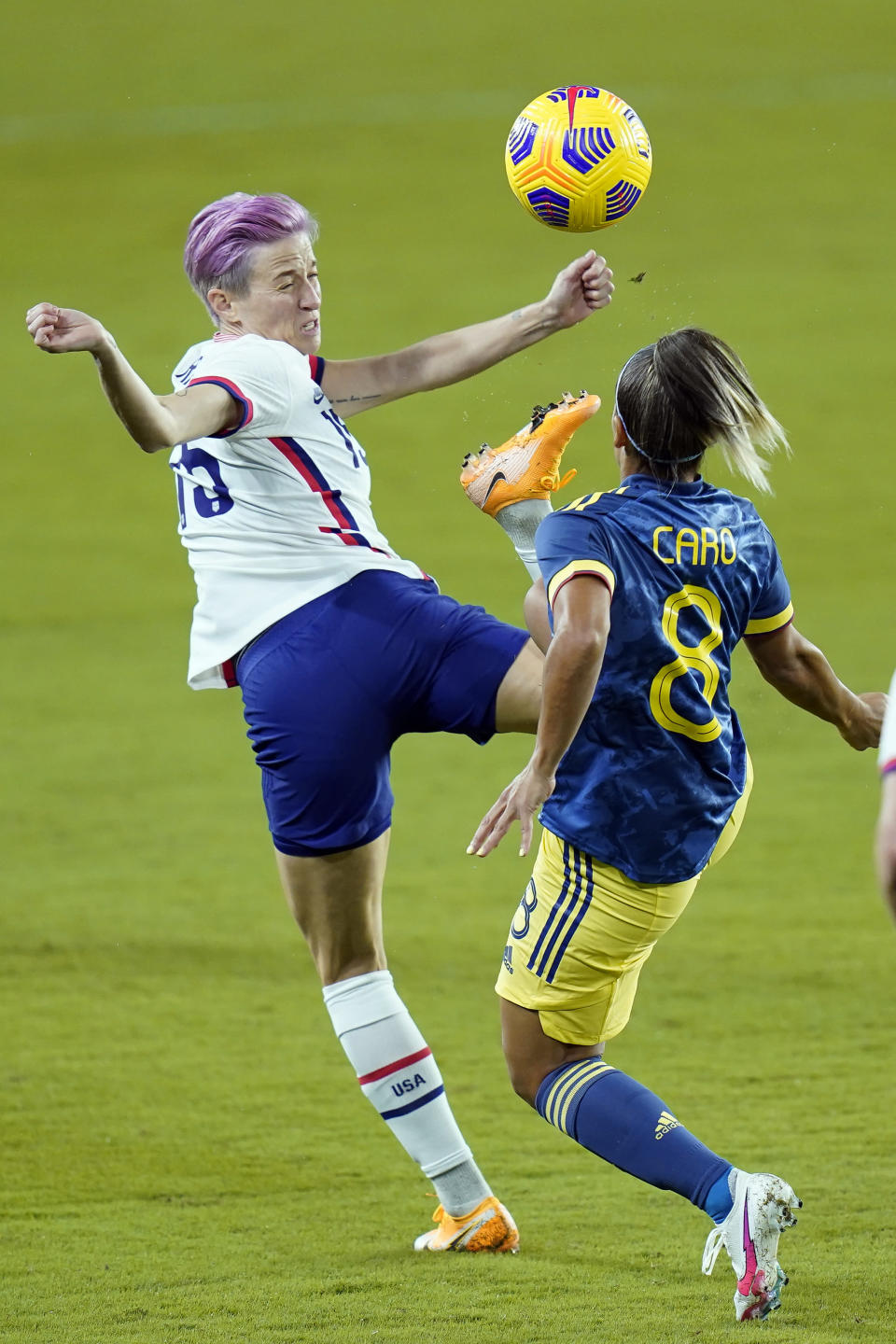 United States forward Megan Rapinoe, left tries to control the ball as she gets in front of Colombia midfielder Jessica Caro (8) during the first half of an international friendly soccer match, Monday, Jan. 18, 2021, in Orlando, Fla. (AP Photo/John Raoux)