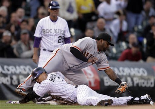 Colorado Rockies' Carlos Gonzalez, bottom, slides safely into third base against San Francisco Giants third baseman Pablo Sandoval on a triple in the first inning of their baseball game in Denver, Wednesday, April 11, 2012. Rockies' Marco Scutaro (not shown) scored on the play. (AP Photo/Joe Mahoney)