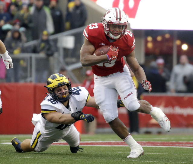 "Wisconsin's <a class=""link rapid-noclick-resp"" href=""/college-football/players/281310/"" data-ylk=""slk:Jonathan Taylor"">Jonathan Taylor</a> runs past Michigan's Chris Hanlon during an NCAA college football game Saturday, Nov. 18, 2017, in Madison, Wis. Taylor ran for 1,977 yards to set the Bowl Subdivision freshman rushing record. (AP Photo/Aaron Gash, File)"