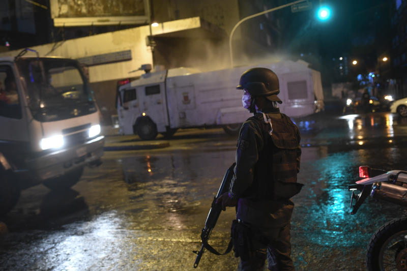 Bolivarian National Guards use a water cannon to spray disinfectant as a preventive measure against the spread of the new coronavirus, in Caracas, Venezuela, Saturday, March 21, 2020. (AP Photo/Matias Delacroix)