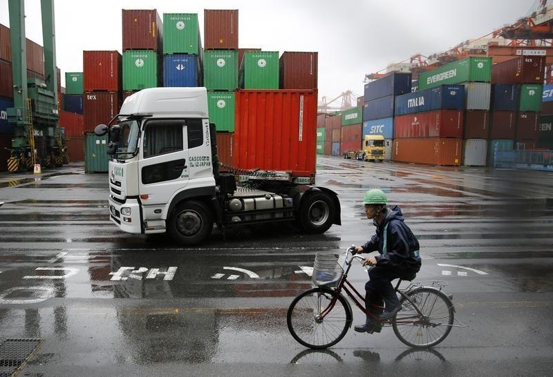 A worker rides a bicycle in a container area at a port in Tokyo