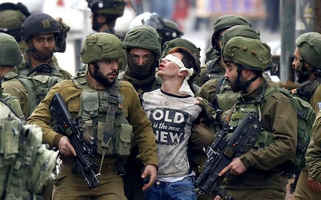 <p>Israeli forces detain a Palestinian protester during clashes in Hebron, West Bank on Dec. 7, 2017, that followed protests against a decision by President Donald Trump to recognize Jerusalem as the capital of Israel. (Photo: APAImages/REX/Shutterstock) </p>