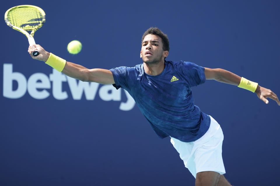 Feliz Auger-Aliassime of Canada reaches for a shot by John Isner during the Miami Open tennis tournament, Sunday, March 28, 2021, in Miami Gardens, Fla. (AP Photo/Marta Lavandier)