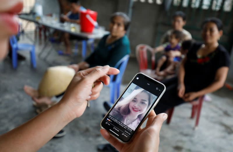 A relative looks at an image of Anna Bui Thi Nhung, a victim who was found dead in the back of British truck, at her home in Nghe An province