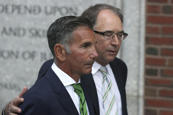 FILE - In this April 3, 2019 file photo, clothing designer Mossimo Giannulli, foreground, departs federal court in Boston after facing charges in a nationwide college admissions bribery scandal. Giannulli has been released from a California prison, Saturday, April 3, 2021 and is currently at a halfway house outside Los Angeles following his imprisonment for his role in a college admissions bribery scheme, records show. (AP Photo/Charles Krupa, File)