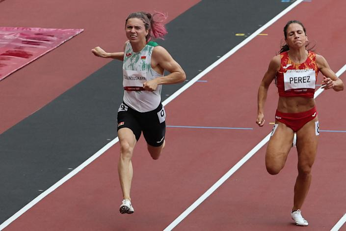 This file photo taken on July 30, 2021 shows Belarus' Krystsina Tsimanouskaya (L) and Spain's Maria Isabel Perez competing in the women's 100m heats during the Tokyo 2020 Olympic Games at the Olympic Stadium in Tokyo. - Poland has granted a humanitarian visa to Krystsina Tsimanouskaya, a Belarusian Olympic athlete who claimed her team tried to force her to leave Japan, Poland's deputy foreign minister said on August 2, 2021. (Photo by Giuseppe CACACE / AFP) (Photo by GIUSEPPE CACACE/AFP via Getty Images)