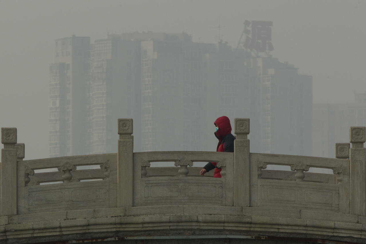 A man wearing a mask walks on a stone bridge in a park on a hazy day in Beijing, China, Monday, Jan. 14, 2013. Beijing schools kept children indoors and hospitals saw a spike in respiratory cases Monday following a weekend of off-the charts pollution in China's smoggy capital, the worst since the government began being more open about air-quality data. (AP Photo/Alexander F. Yuan)