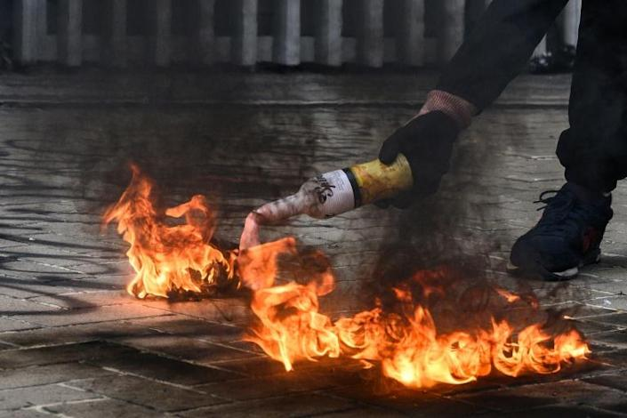 A protester in Hong Kong uses a fire to light a Molotov cocktail before throwing it towards police outside the city's government headquarters (AFP Photo/ANTHONY WALLACE)