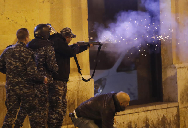 A riot police officer fires rubber bullets towards anti-government protesters trying to enter parliament square in downtown Beirut, Lebanon, Saturday, Dec. 14, 2019. The recent clashes marked some of the worst in the capital since demonstrations began two months ago. The rise in tensions comes as politicians have failed to agree on forming a new government. (AP Photo/Hussein Malla)