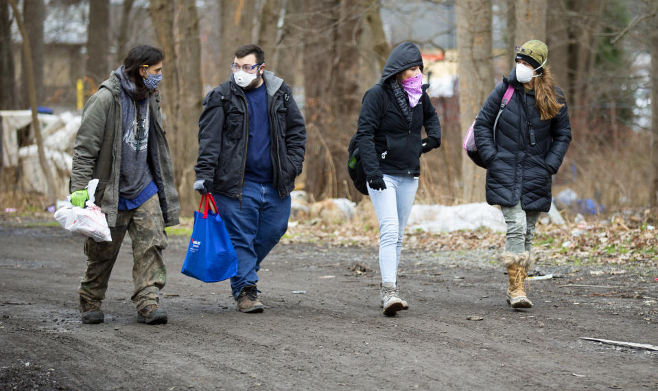 Jose Ortiz, left, a resident of the homeless encampment known as the Jungle, walks with Matt Dankanich, a community health worker for REACH Medical; Tas'a Towsley, a friend of Ortiz; and Deb Wilke, right, the homeless crisis alleviation coordinator for Second Wind Cottages, Monday, Dec. 7, 2020, in Ithaca, N.Y. The pandemic has caught homeless service providers in a crosscurrent: demand is high, but their ability to provide services are constricted. (AP Photo/John Munson)