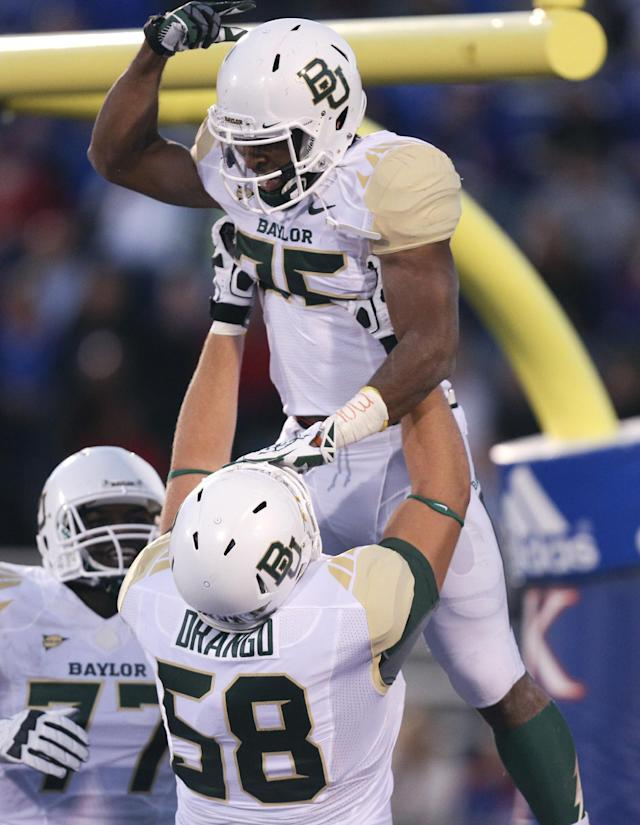 Baylor Bears running back Lache Seastrunk, top, is hoisted into the air by Spencer Drango (58) after scoring in the first quarter of an NCAA college football game against the Kansas Jayhawks, Saturday, Oct. 26, 2013, in Lawrence, Kan. (AP Photo/Ed Zurga)