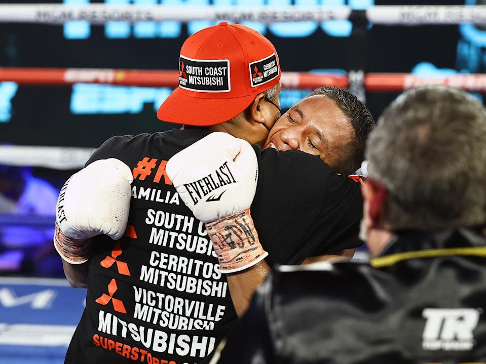 Joshua Franco embraces trainer Robert Garcia after defeating Andrew Moloney Tuesday in Las Vegas to win the WBA super flyweight world title. (Mikey Williams/Top Rank)
