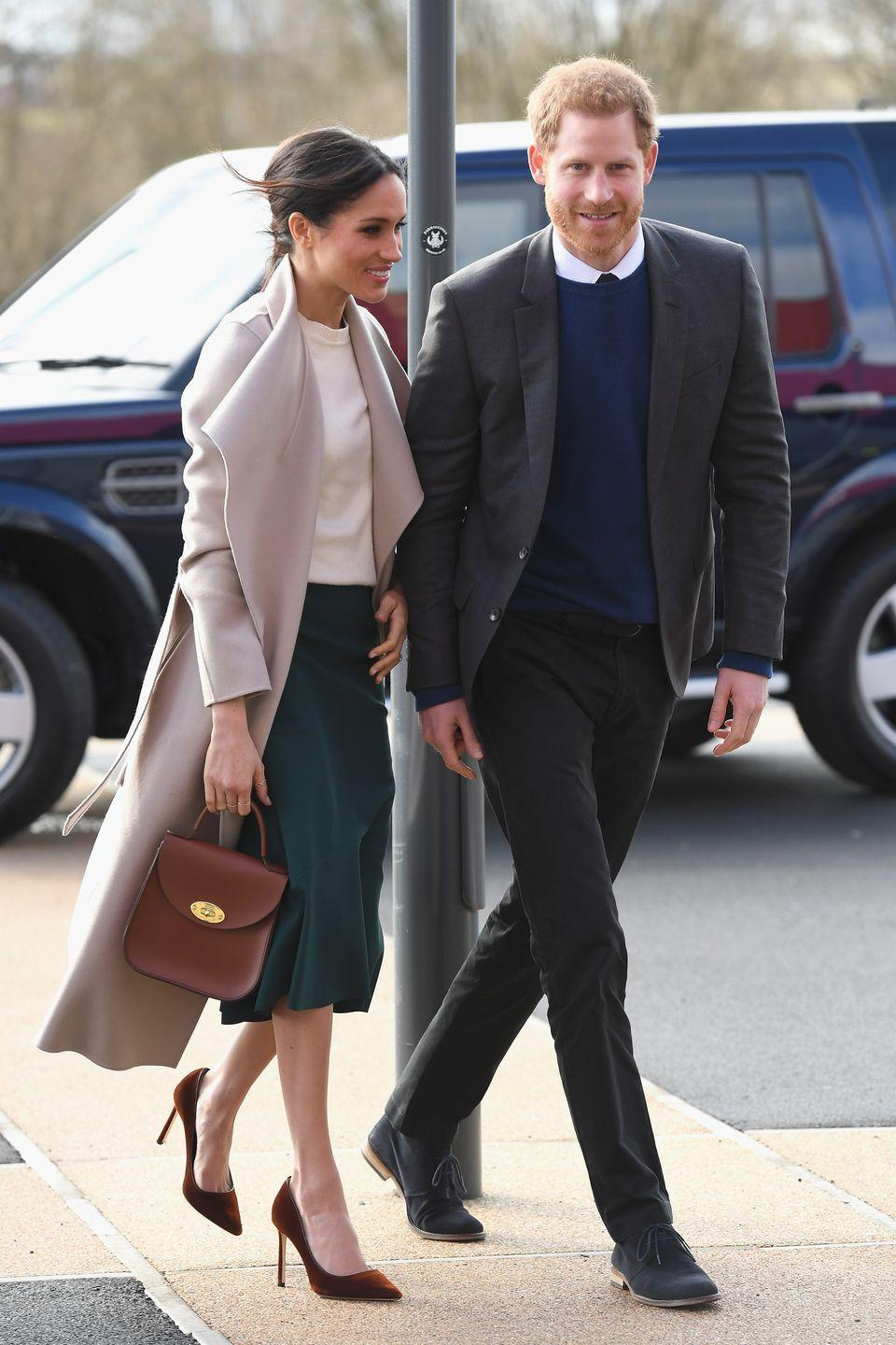 <p>For a surprise visit to Belfast, Markle chose a dusty pink coat over a white shirt and vibrant green skirt. She paired the look with a top-handled bag and maroon stilettos.</p>