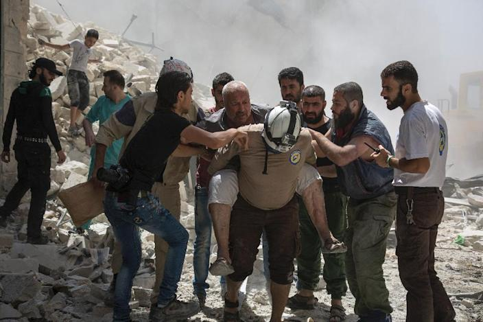 Syrians carry a wounded man following a reported barrel bomb attack by government forces in the opposition-held district of Al-Mashhad near Aleppo on July 26, 2016 (AFP Photo/Karam Al-Masri)