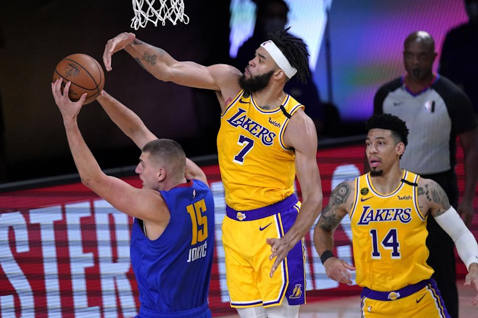 Denver Nuggets center Nikola Jokic (15) comes down with a rebound in front of Los Angeles Lakers' JaVale McGee.