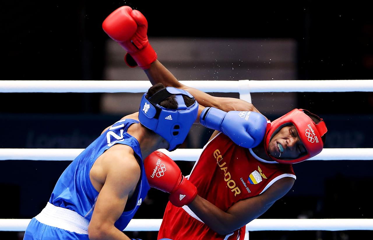 LONDON, ENGLAND - JULY 31:  Anderson Mina Rojas of Equador (R) in action with Uktamjon Rahmonov of Uzbekistan during the Men's Light Welter (64kg) Boxing on Day 4 of the London 2012 Olympic Games at ExCeL on July 31, 2012 in London, England.  (Photo by Scott Heavey/Getty Images)