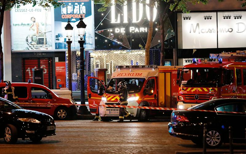Firefighters and rescuers stand by the site of a shooting on the Champs Elysees in Paris on April 20, 2017 - AFP