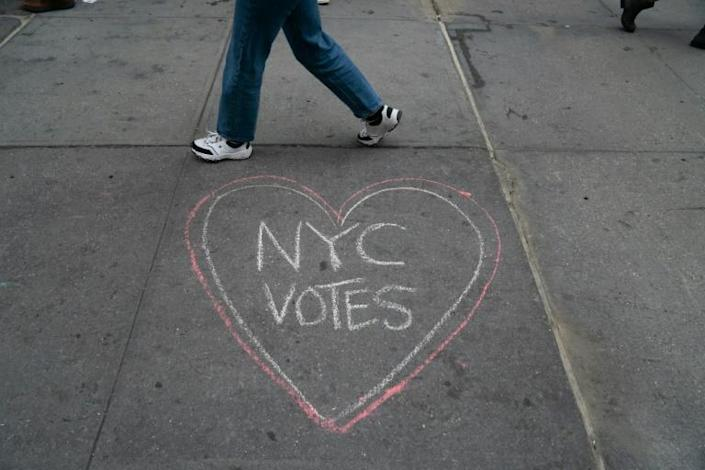 People walk past chalk messages on the sidewalk outside New York's Madison Square Garden on the first day of early voting there on October 24, 2020