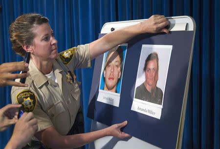 Metro Police Officer Laura Meltzer posts photos of the two shooting suspects Jerad and Amanda Miller during a news conference at Metro Police headquarters in Las Vegas June 9, 2014. REUTERS/Las Vegas Sun/Steve Marcus