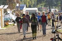 Climate activist Vanessa Nakate from Uganda, front right, visits an activists camp near the Garzweiler open-cast coal mine in Luetzerath, western Germany, Saturday, Oct. 9, 2021. The village of Luetzerath, now almost entirely abandoned as the mine draws ever closer, will be the latest village to disappear as coal mining at the Garzweiler mine expands. Garzweiler, operated by utility giant RWE, has become a focus of protests by people who want Germany to stop extracting and burning coal as soon as possible. (AP Photo/Martin Meissner)