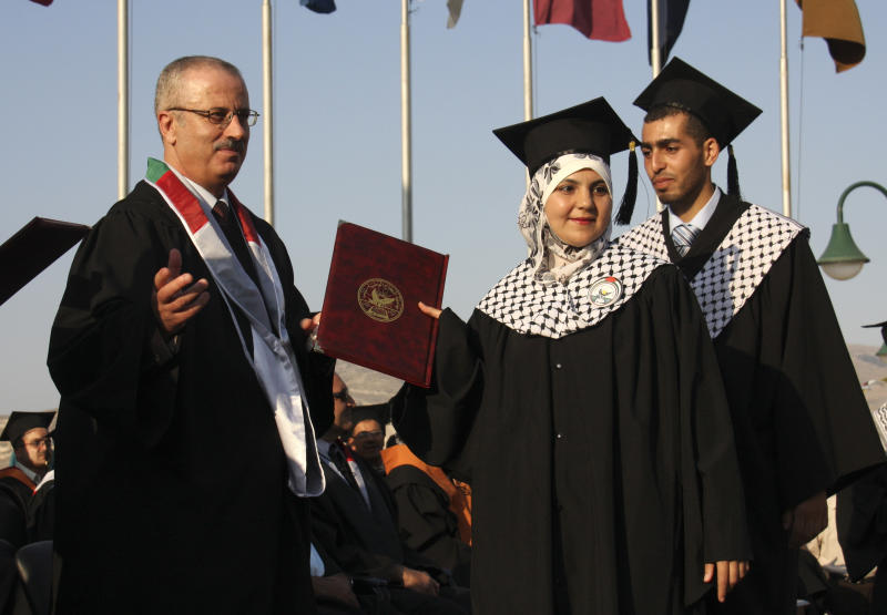 In this June 15, 2011 photo, Dr. Rami Hamdallah, left, a president of the al-Najah University attends the graduation ceremony in Nablus. The Palestinian president Mahmoud Abbas on Sunday June 2, 2013, picked a little-known academic, Dr. Rami Hamdallah, as his new prime minister, according to the official government news agency, following the resignation of his chief rival. (AP Photo/Nasser Ishtayeh)