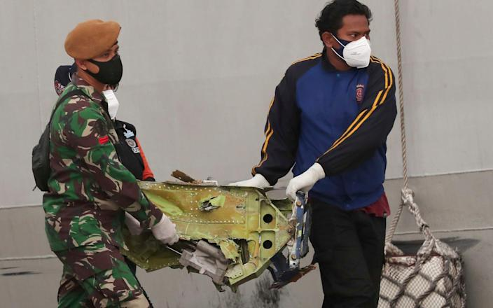 A soldier and rescuer carry debris found in the waters near the crash site - Tatan Syuflana/AP