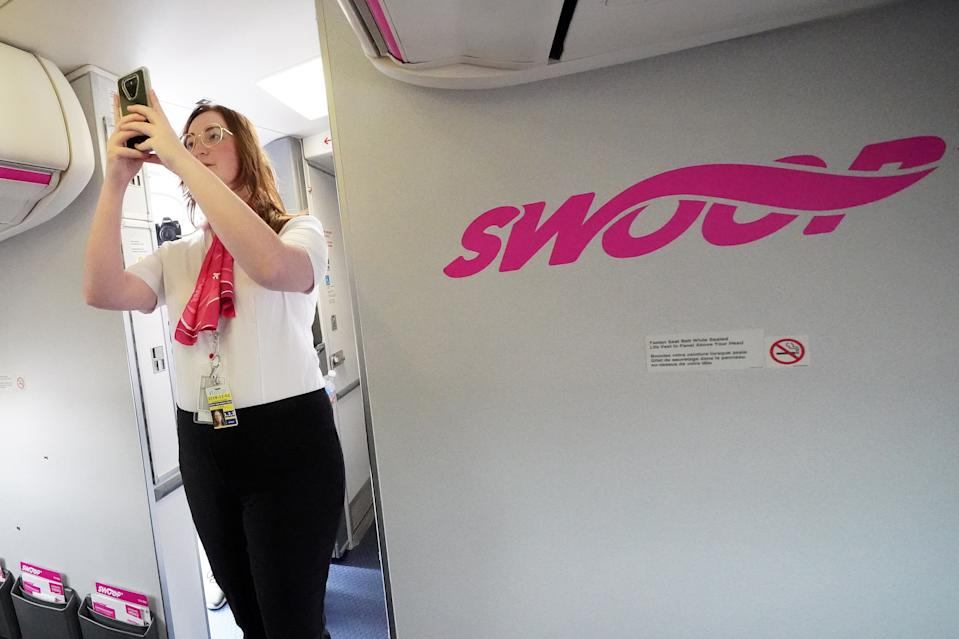 Employees walk onto a plane during a presentation by WestJet celebrating Canada's first ultra low cost airline, Swoop, at John C. Munro Hamilton International Airport in Hamilton, Ontario, Canada, June 19, 2018.  REUTERS/Carlo Allegri