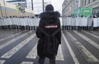 FILE - In this Sunday, Jan. 31, 2021 file photo, a man with a sign 'Navalny' on his back stands in front of riot policemen blocking the way to protester during a protest against the jailing of opposition leader Alexei Navalny in St. Petersburg, Russia. A prison sentence for Russian opposition leader Alexei Navalny and a sweeping crackdown on protesters demanding his release reflect the Kremlin's steely determination to fend off threats to its political monopoly at any cost. (AP Photo/Dmitri Lovetsky, File)