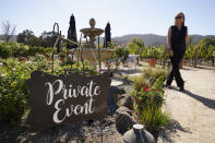 Event planner Janice Twomey looks over a garden area where weddings were often held at Brix Napa Valley near Oakville, Calif., on Thursday, Oct. 15, 2020. In three of the past four years, major wildfires driven by a changing climate have devastated parts of the world-class region, leaving little doubt that it's vulnerable to smoke, flames and blackouts during the fall. (AP Photo/Eric Risberg)