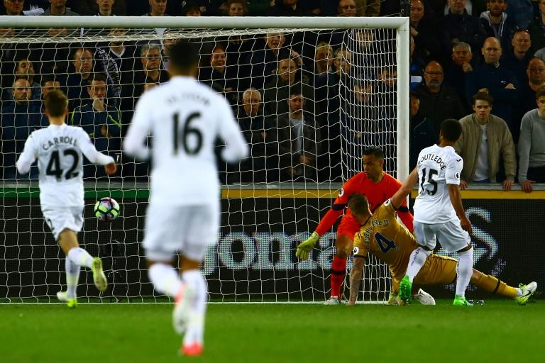 Swansea City's midfielder Wayne Routledge (R) scores the opening goal of the English Premier League football match between Swansea City and Tottenham Hotspur at The Liberty Stadium in Swansea, south Wales on April 5, 2017