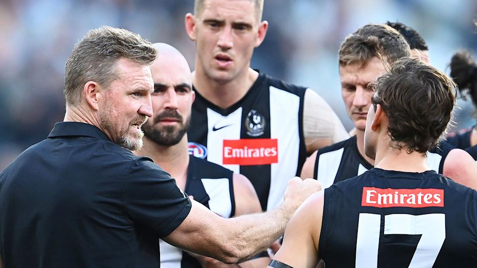 Pictured here, Nathan Buckley speaks to his Magpies players during an AFL game.