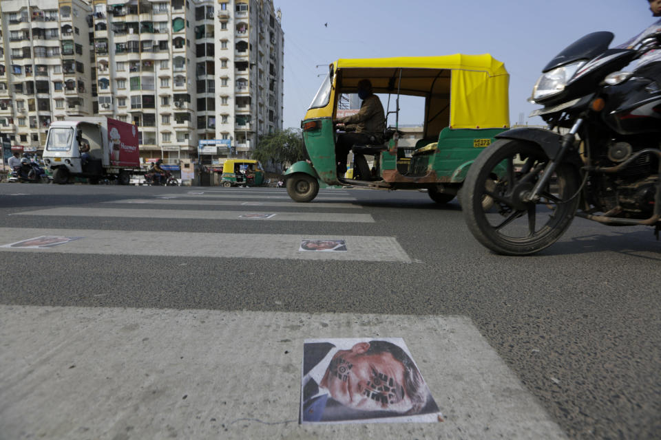 Indian commuters move on defaced images of French President Emmanuel Macron pasted by protestors on a road in Ahmedabad, India, Sunday, Nov. 1, 2020. Muslims have been calling for both protests and a boycott of French goods in response to France's stance on caricatures of Islam's most revered prophet. (AP Photo/Ajit Solanki)